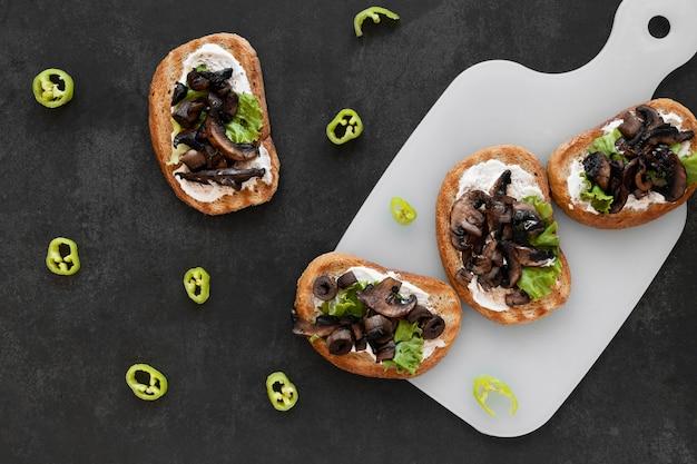 Bovenaanzicht arrangement van heerlijke broodjes op zwarte achtergrond Gratis Foto