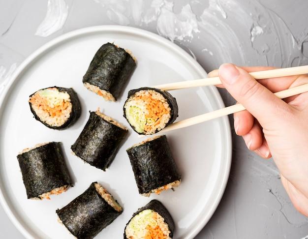 Bovenaanzicht assortiment van sushi rolt met stokjes Gratis Foto