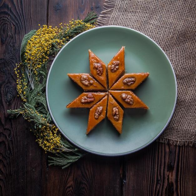 Bovenaanzicht baklava met mimosa bloemen in ronde plaat Gratis Foto