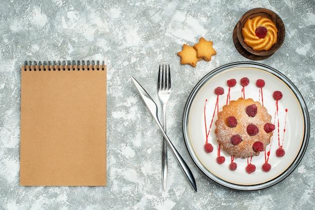 Bovenaanzicht berry cake op witte ovale plaat koekjes in kom vork en diner mes notebook op grijze ondergrond Gratis Foto