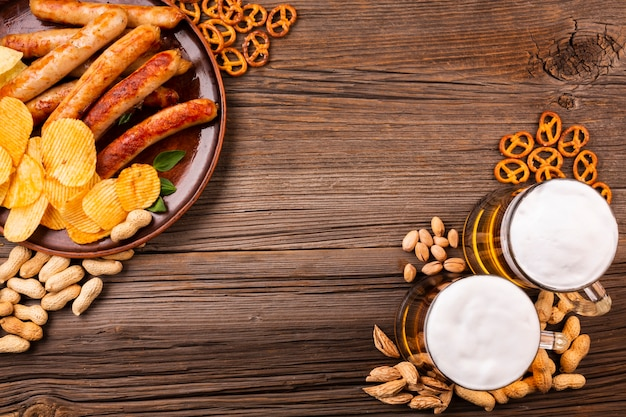 Bovenaanzicht bier met voedsel op houten tafel Gratis Foto