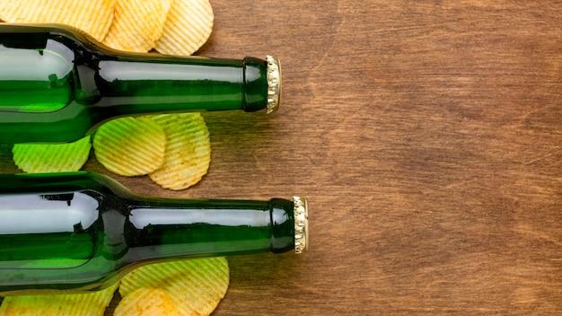 Bovenaanzicht bierflesjes en chips met kopie-ruimte Gratis Foto