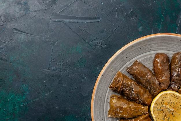 Bovenaanzicht blad dolma heerlijke oosterse vleesmaaltijd gerold in groene bladeren op donkerblauw bureau Gratis Foto