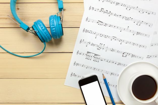 Bovenaanzicht bladmuziek notitiepapier en kerstversiering op houten achtergrond Premium Foto