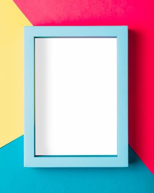 Bovenaanzicht blauw frame op kleurrijke achtergrond Gratis Foto