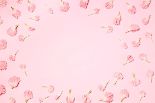 Bovenaanzicht bloemblaadjes op roze achtergrond Gratis Foto