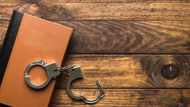 Bovenaanzicht boek en handboeien op houten tafel Premium Foto