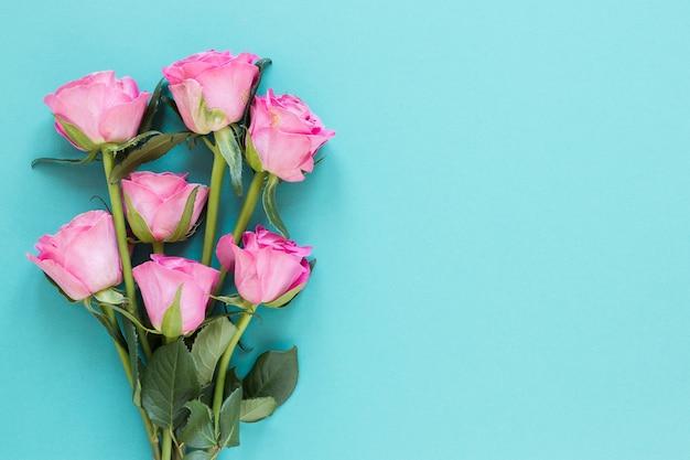Bovenaanzicht boeket rozen op blauwe kopie ruimte achtergrond Gratis Foto