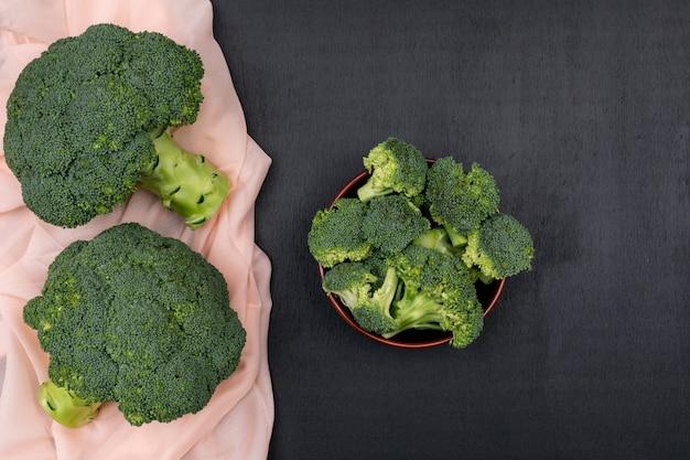Bovenaanzicht bos van broccoli op roze doek met broccoli in keramische kom Gratis Foto