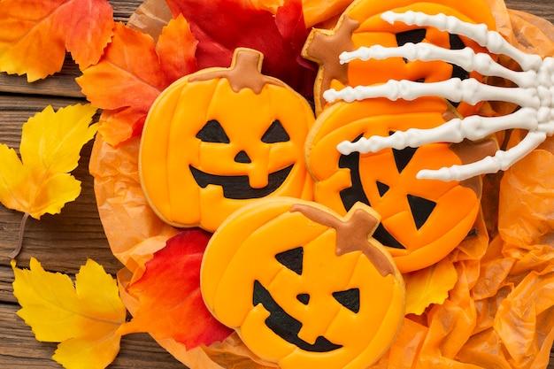 Bovenaanzicht boze halloween pompoenen met skelet hand Gratis Foto