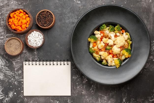 Bovenaanzicht broccoli en bloemkoolsalade in zwarte kom verschillende kruiden en wortel snijden in kommen een notitieboekje op donkere ondergrond Gratis Foto
