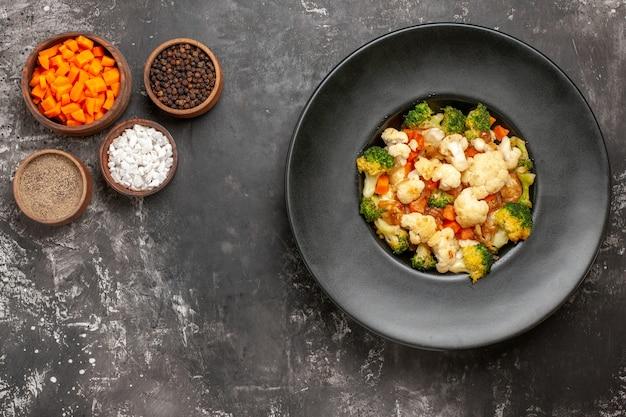 Bovenaanzicht broccoli en bloemkoolsalade in zwarte kom verschillende kruiden en wortel snijden in kommen op donkere ondergrond met kopie ruimte Gratis Foto