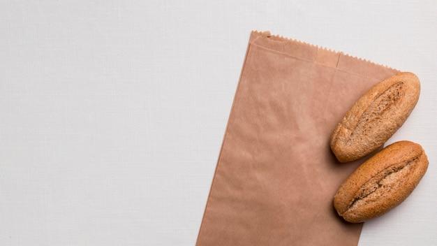 Bovenaanzicht brood en papieren verpakkingen met kopieerruimte Gratis Foto