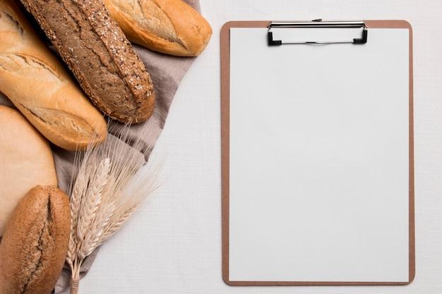 Bovenaanzicht broodmix met leeg klembord Gratis Foto