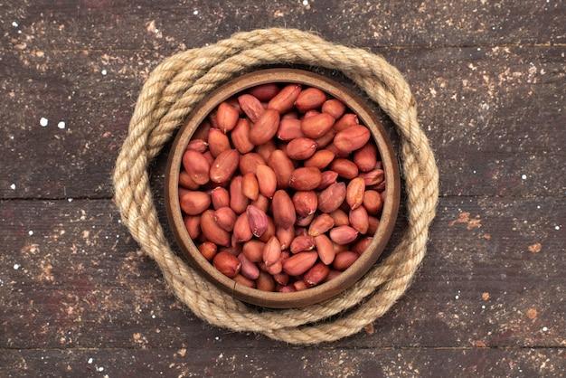 Bovenaanzicht bruine rauwe noten in ronde kom met touwen op bruin, noten walnoot snack zout Gratis Foto
