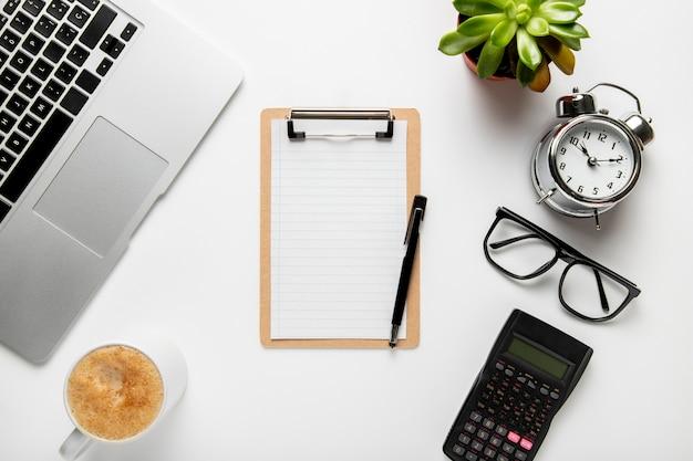 Bovenaanzicht bureau met klembord en klok Gratis Foto