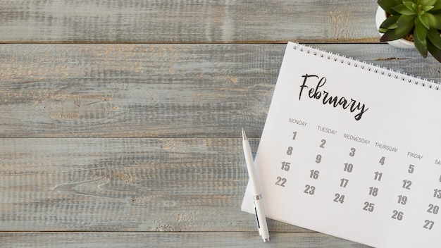 Bovenaanzicht bureaukalender op lichte houten tafel Premium Foto