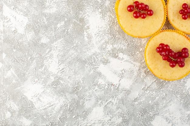 Bovenaanzicht cake met cranberries heerlijk en perfect gebakken op de lichte achtergrond cake koekje suiker zoet Gratis Foto