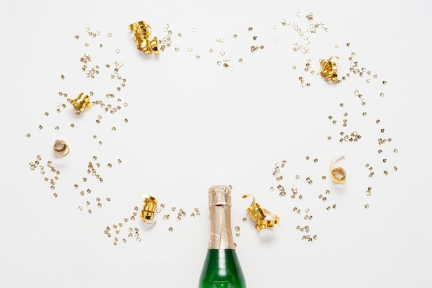 Bovenaanzicht champagnefles met gouden linten en confetti Gratis Foto