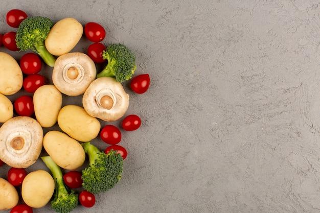 Bovenaanzicht champignons samen met rode kerstomaten en broccoli vers rijp op de lichte vloer Gratis Foto
