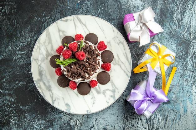 Bovenaanzicht cheesecake met chocolade op ovale plaat kerstcadeaus op grijze ondergrond Gratis Foto