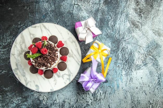 Bovenaanzicht cheesecake met chocolade op ovale plaat kerstcadeaus op grijze oppervlakte vrije ruimte Gratis Foto