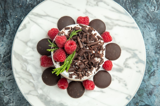Bovenaanzicht cheesecake met chocolade op witte ovale plaat op de grijze foto van het oppervlakvoedsel Gratis Foto