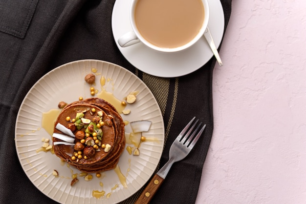 Bovenaanzicht chocolade pannenkoeken met hazelnoten, kiwi, kokosvlokken en ahornsiroop in beige plaat met witte kop koffie op keukenschort op roze achtergrond Premium Foto