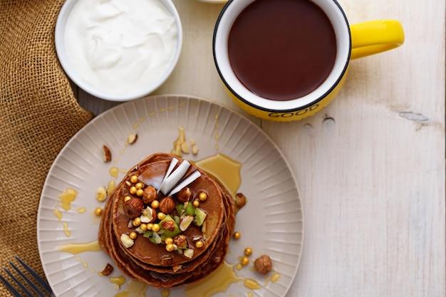 Bovenaanzicht chocolade pannenkoeken met kiwi, hazelnoot, honing op plaat met zure room en kopje cacao op witte achtergrond Premium Foto