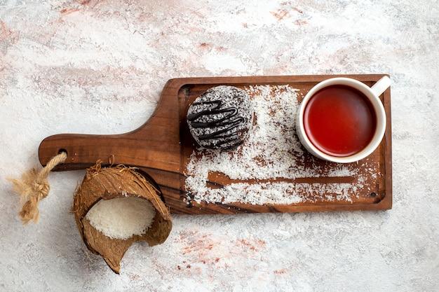 Bovenaanzicht chocoladetaart met kopje thee op lichte witte achtergrond chocoladetaart koekje suiker zoet koekje Gratis Foto