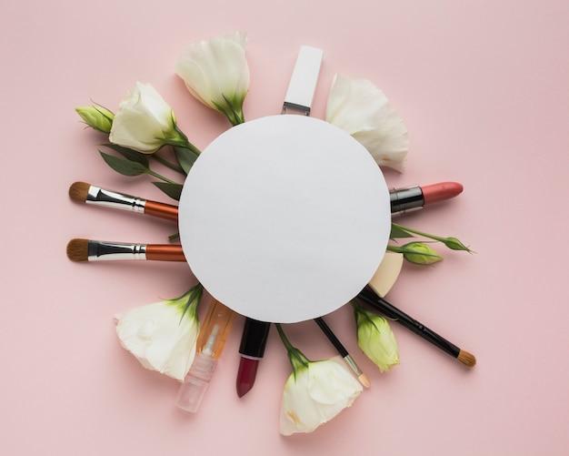 Bovenaanzicht cirkelvormig arrangement met make-up en bloemen Gratis Foto