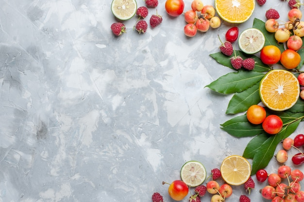 Bovenaanzicht citroenen en kersen vers fruit op het licht bureau fruit vers zacht rijp Gratis Foto