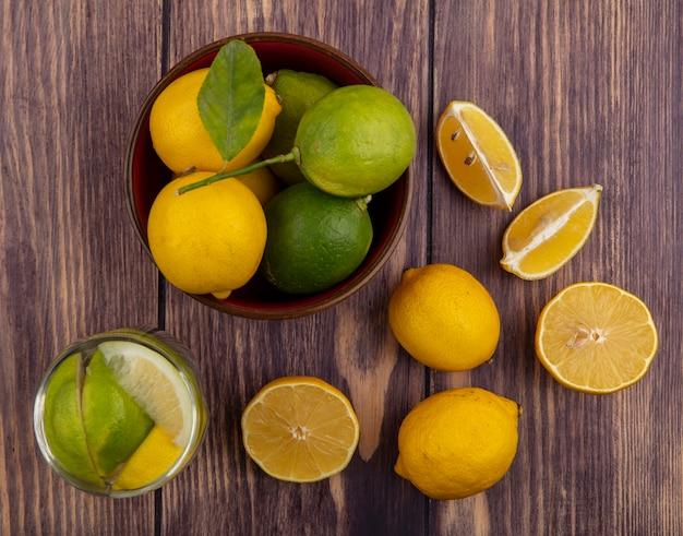 Bovenaanzicht citroenen met limoenen in kom en glas detoxwater op hout achtergrond Gratis Foto