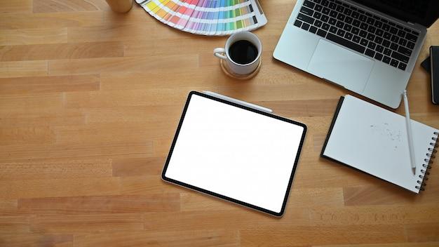 Bovenaanzicht creatieve tafel met tablet, laptopcomputer, kleurengids en koffie op houten bureau. Premium Foto