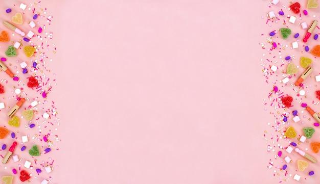 Bovenaanzicht decoratie geassorteerde kleverige snoepjes en jelly snoepjes gelukkig vakantie concept. plat lag kleurrijke snoep op mooie roze bureau. kopieer ruimte. Premium Foto