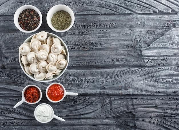 Bovenaanzicht deeg in kom met saus, kruiden op grijze houten oppervlak. horizontale ruimte voor tekst Gratis Foto