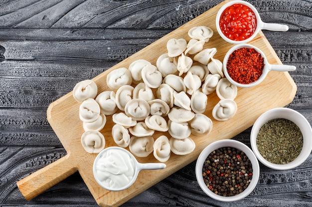 Bovenaanzicht deeg op een snijplank met saus, kruiden in kommen op grijze houten oppervlak. horizontaal Gratis Foto