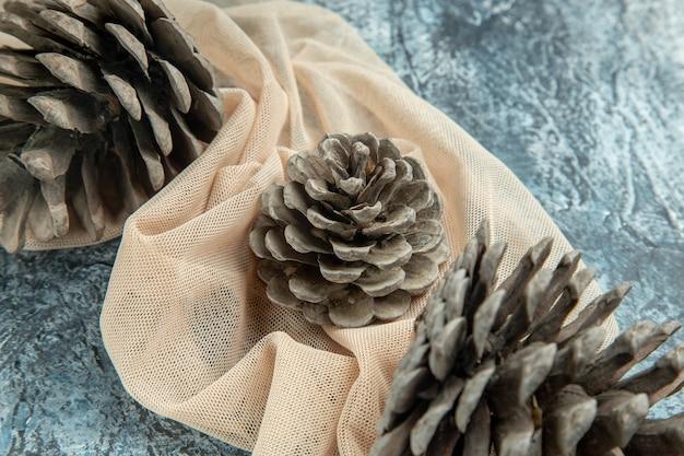 Bovenaanzicht dennenappels op beige sjaal op donkere ondergrond Gratis Foto