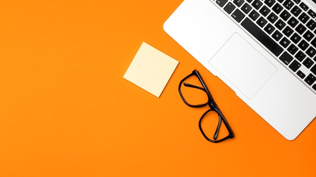 Bovenaanzicht desk concept met oranje achtergrond Gratis Foto