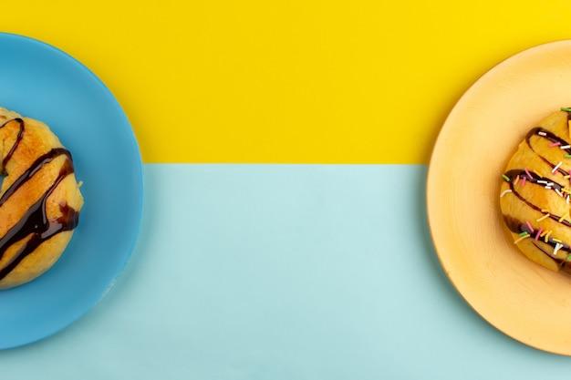 Bovenaanzicht donuts zoete lekkere binnenkant platen op de kleurrijke achtergrond Gratis Foto