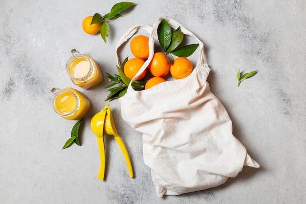 Bovenaanzicht draagtas met sinaasappels en sap Gratis Foto