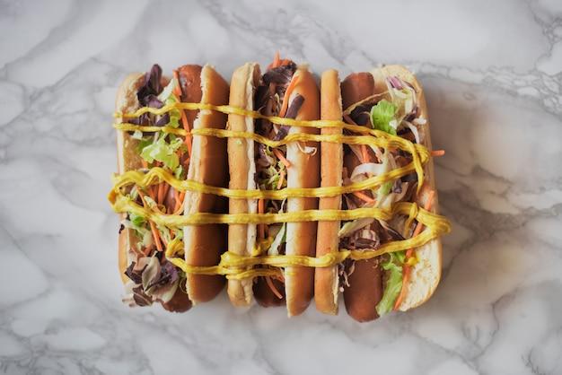 Bovenaanzicht drie hotdogs met mosterd Gratis Foto