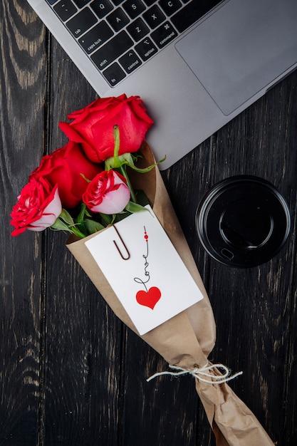 Bovenaanzicht een boeket van rode rozen in ambachtelijke papier met briefkaart in bijlage ligt in de buurt van een laptop met een papieren kopje koffie op donkere houten achtergrond Gratis Foto