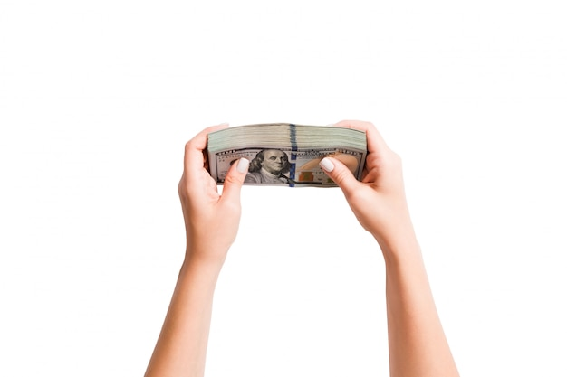 Bovenaanzicht een bundelgeld in vrouwelijke handen. beeld tellende dollars op geïsoleerd wit. belasting Premium Foto