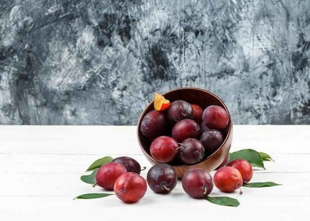 Bovenaanzicht een kom pruimen en aardbeien op rieten placemat op wit houten bord en donkerblauw marmeren oppervlak. Gratis Foto
