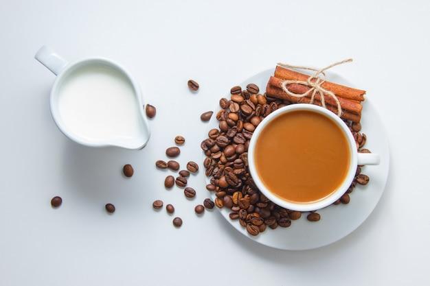 Bovenaanzicht een kopje koffie met koffiebonen en droge kaneel op schotel en met melk, op witte ondergrond Gratis Foto