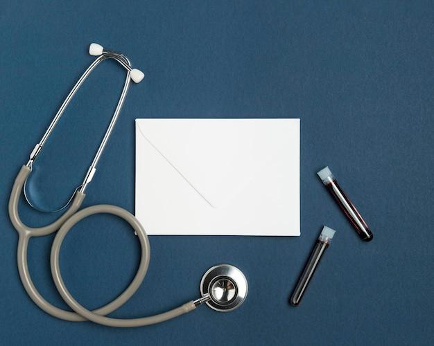 Bovenaanzicht envelop met medische stethoscoop Gratis Foto