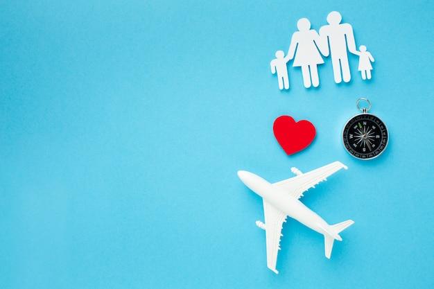 Bovenaanzicht familie figuur met papieren vliegtuig en kompas Gratis Foto