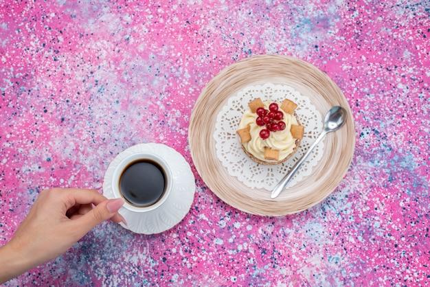 Bovenaanzicht femlae koffie drinken met slagroomtaart op de gekleurde achtergrond cake crème kleur deeg bakken Gratis Foto
