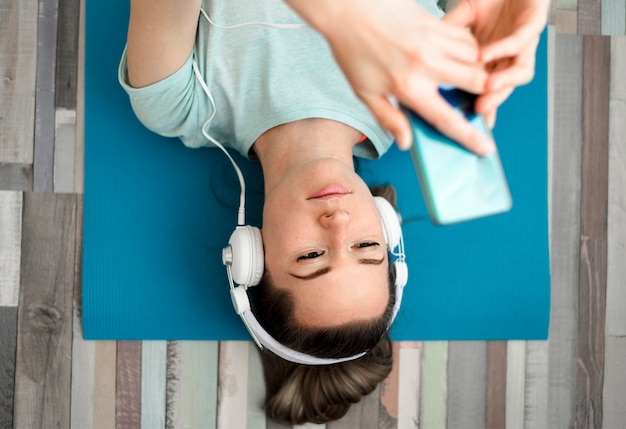 Bovenaanzicht fit vrouw, luisteren naar muziek Gratis Foto